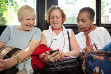 Woman showing smart phone to friends while traveling in bus