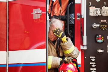 Exhausted fireman sitting in fire engine