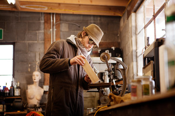 Man shaping wood on machinery at workshop