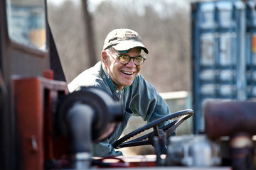 Senior man laughing while sitting in forklift