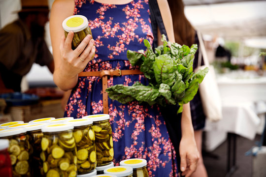 Midsection of woman carrying chard holding pickled okras jar at market