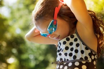 Girl fastening swimming goggles