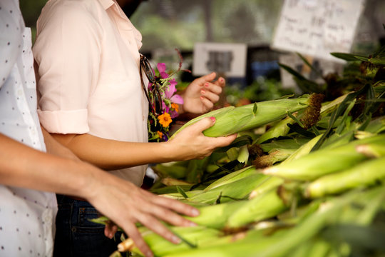 Midsection of women buying corns at market