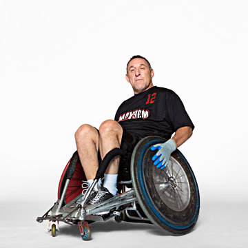 Portrait of smiling player siting on wheelchair against white background