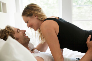 Side view of couple smiling while lying on bed at home