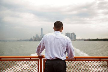 Rear view of man standing at railing on ferry against cloudy sky