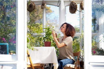Woman examining plant while sitting on chair at greenhouse Wall mural
