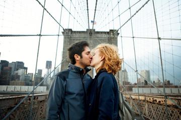 Romantic couple kissing on Brooklyn Bridge