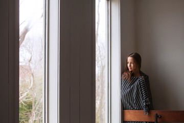 Woman wrapped in shawl looking away while standing by wall at home