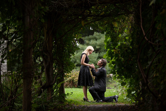 Man proposing to woman on grassy field