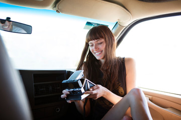 Happy woman watching instant camera while sitting in camper van