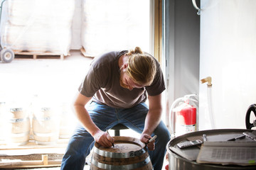 Worker writing on barrel at distillery