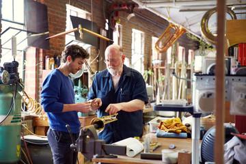 Men repairing trumpet while working in workshop