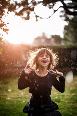 Cheerful girl playing with water on field