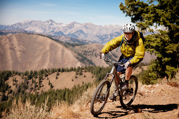 Confident hiker riding bicycle on mountain