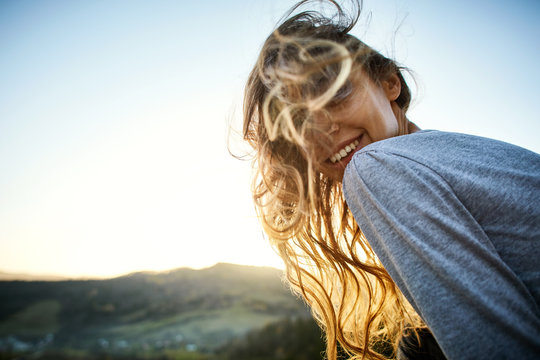 portrait of smiling cheerful woman with long hair sitting on edge of cliff against background of sunrise. woman's hair fluttering beautifully in the wind
