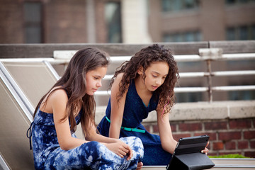 Siblings using tablet while sitting on deck chairs at building terrace