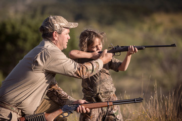 Girl aiming with rifle while man assisting her on grassy field