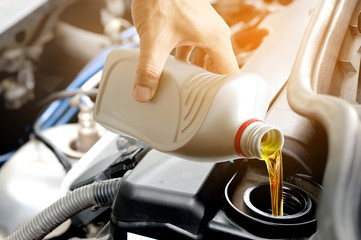 Refueling and pouring oil into the engine motor car. Energy fuel concept.