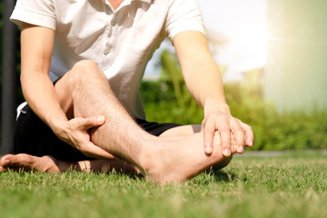 Foot pain .Woman sitting on grass Her hand caught at the foot. Having painful feet and stretching muscles fatigue To relieve pain. health concepts.