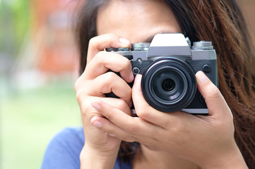 hipster lifestyle of cute girl She holds a camera. And save photos On a digital camera.Travel and Lifestyle concept