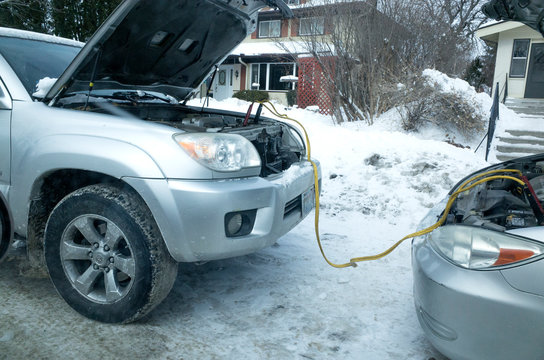 Starting stalled car with jumper cables attached battery to battery from another auto. St Paul Minnesota MN USA