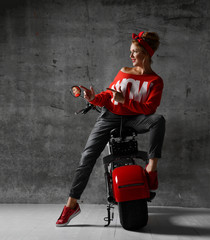 Woman sitting on motorcycle bicycle scooter  retro pinup style point hands at the corner in red blouse and jeans