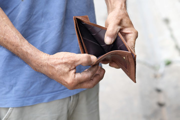 hand of woman grab a coin gold from he wallet brown to be used in the shopping..Money and spending ideas