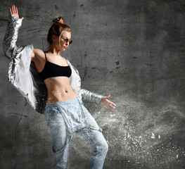 Woman workout exercise stand in silver sexy down puffer jacket blue jeans sunglasses on loft wall with dust snow splashes