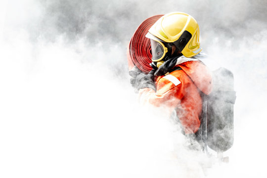 Firefighter in the midst of fire and smoke.