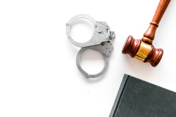Crime concept. Metal handcuffs near judge gavel and law book on white background top view copy space