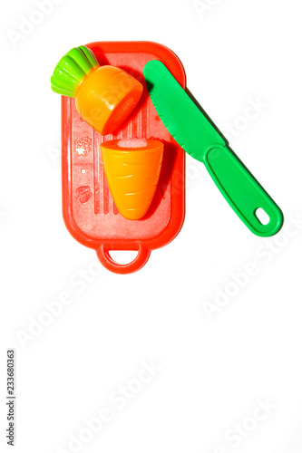257bbb16799d56 childrens plastic toy. plastic carrot on red cutting board with green knife  isolated on white background in soft-focus in the background