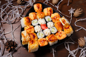 New Year's assortment of sushi on a black plate, with garlands. Christmas New Year sushi set.