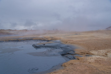 Bubbles rise in hot mud in this steamy geothermal Icelandic landscape scene