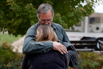 Walker comforts his wife at an evacuation center for people displaced by the Camp Fire in Chico