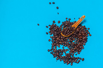 Coffee beans spilled on a bright blue background