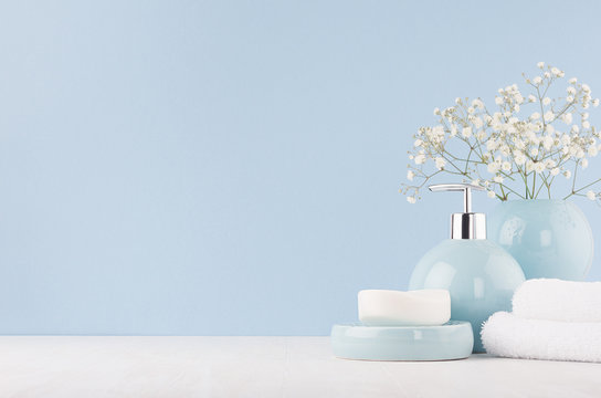 Soft light fresh bathroom interior in pastel blue color with white bouquet, smooth ceramic bowls, cosmetic products on wood table.