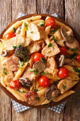 Penne pasta with chicken, mushrooms, smoked sausage, covered with cream cheese sauce close-up. Vertical top view