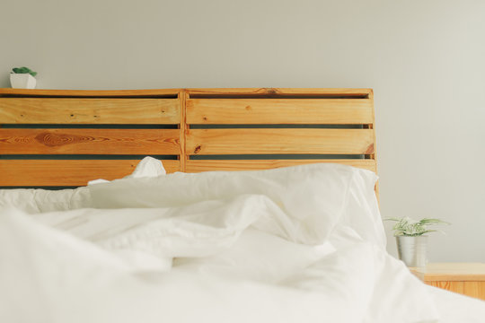 Loft style unmaking bed with wooden headboard.
