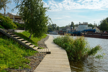 Rustic wooden walkway along the river. Countryside. Old rusty ships in the background. Summer time