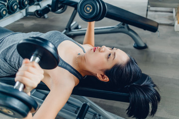 Woman workout for dumbbell bench press in the fitness gym.