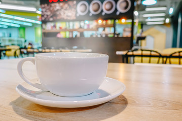 Cup of coffee on wood table in cafe in vintage color mood