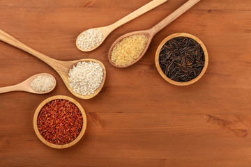 An assortment of rice types, shot from above on a rustic wooden background with copy space. Red, black, yellow, Asian, Spanish and Italian rices with a place for text