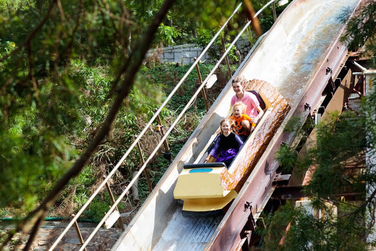 Family with kids on roller coaster in theme park.
