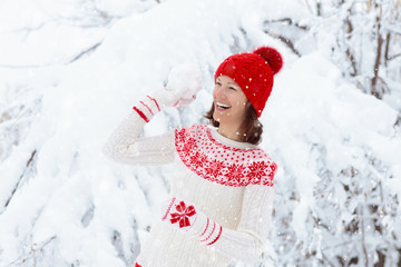 Woman in sweater playing snow ball fight in winter
