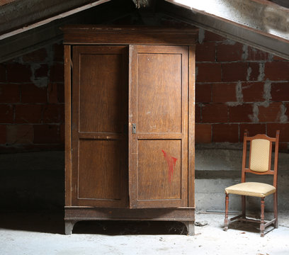 dusty attic of the house with a wooden wardrobe and an old ramsh