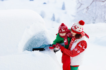 Mother and child brushing off car in winter.