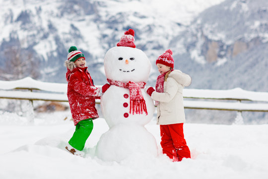 Child building snowman. Kids build snow man.