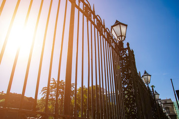 Tall iron fence with ancient street lights perspective. Toned image