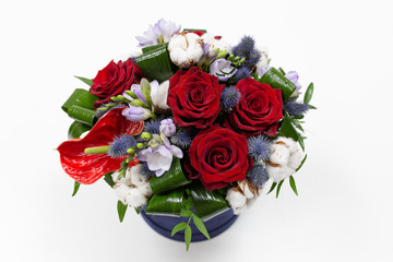 A bright bouquet of red flowers (rose and anthurium) with green leaves, Alstroemeria and cotton flowers in a blue box for hats on a light background